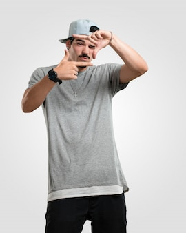 Homem jovem rapper fazendo uma forma de quadro com as mãos, tentando se concentrar como se fosse uma câmera