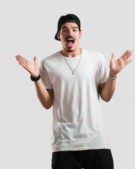 Homem jovem rapper gritando feliz, surpreso por uma oferta ou uma promoção, pasmado, pulando e orgulhoso