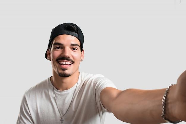 Homem jovem rapper sorrindo e feliz, tomando um selfie