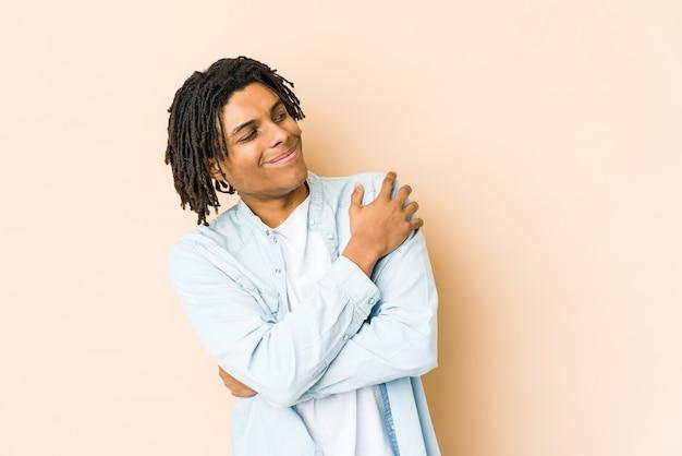 Homem jovem rasta americano africano abraços, sorrindo despreocupado e feliz.