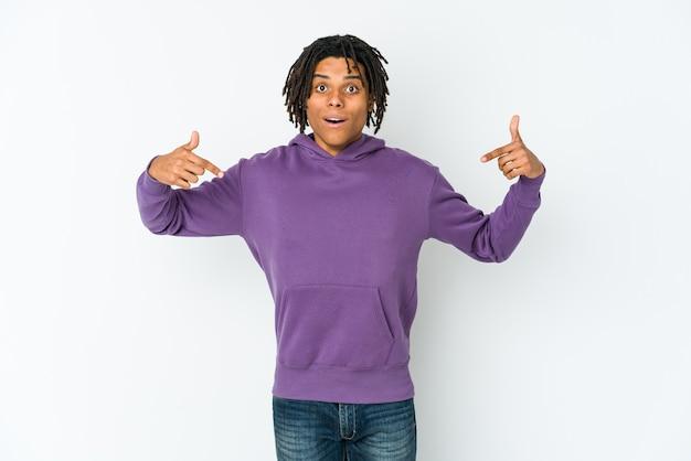 Homem jovem rasta americano africano aponta para baixo com os dedos, sentimento positivo.