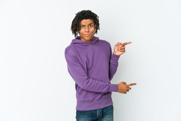 Homem jovem rasta americano africano apontando com o dedo indicador para um copyspace.