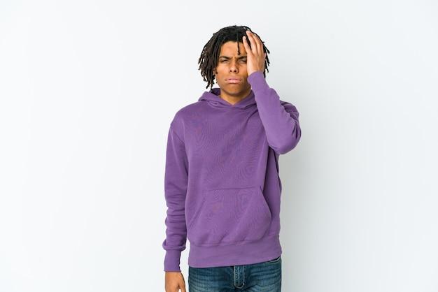 Homem jovem rasta americano africano cansado e com muito sono, mantendo a mão na cabeça.