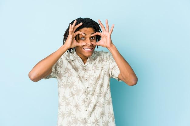 Homem jovem rasta americano africano mantendo os olhos abertos para encontrar uma oportunidade de sucesso.