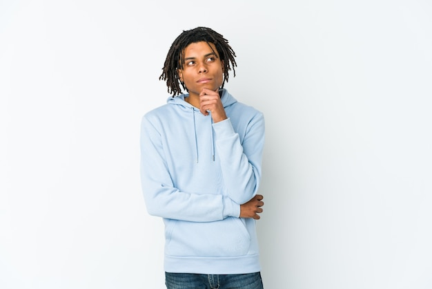 Homem jovem rasta americano africano olhando de soslaio com expressão duvidosa e cética.