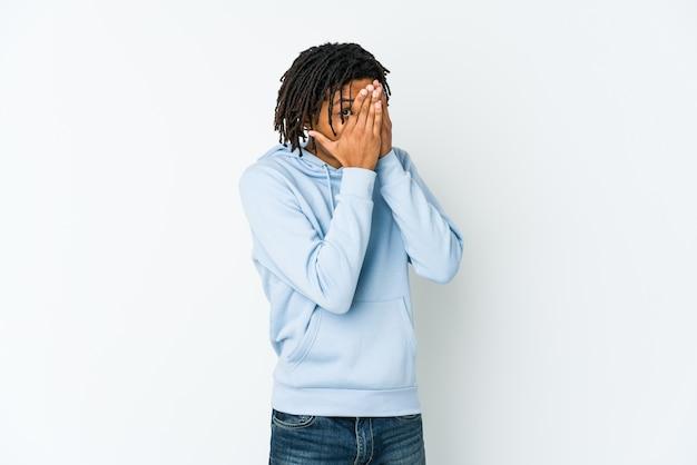 Homem jovem rasta americano africano pisca por entre os dedos assustado e nervoso.