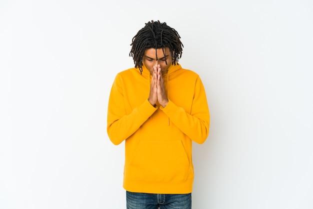 Homem jovem rasta americano africano rezando, mostrando devoção, pessoa religiosa em busca de inspiração divina.