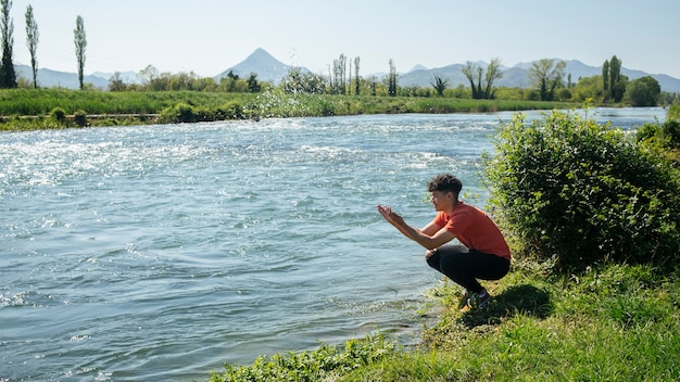Homem jovem, respingue água, de, rio