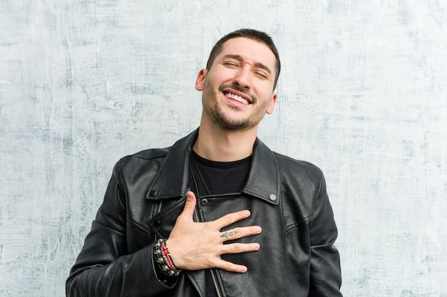 Homem jovem roqueiro ri em voz alta, mantendo a mão no peito.