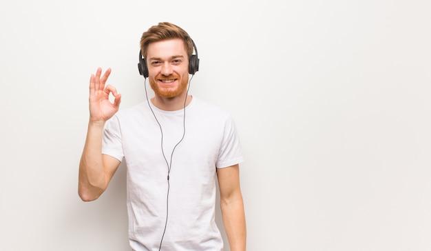 Homem jovem ruiva alegre e confiante, fazendo o gesto de ok e ouvir música com fones de ouvido