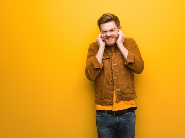 Homem jovem ruiva cobrindo as orelhas com as mãos