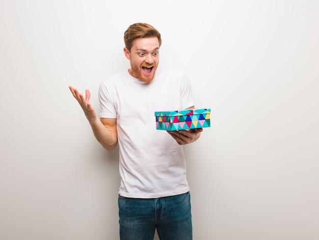 Homem jovem ruiva comemorando uma vitória ou sucesso. segurando uma caixa de presente.