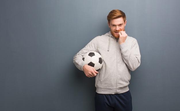 Homem jovem ruiva fitness roer unhas, nervoso e muito ansioso. ele está segurando uma bola de futebol.