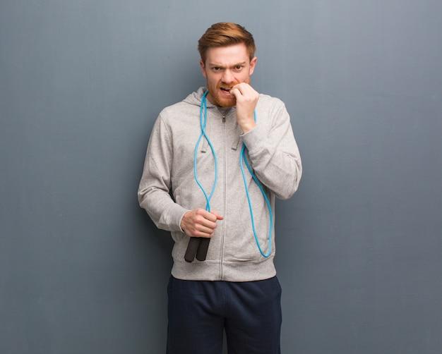 Homem jovem ruiva fitness roer unhas, nervoso e muito ansioso.