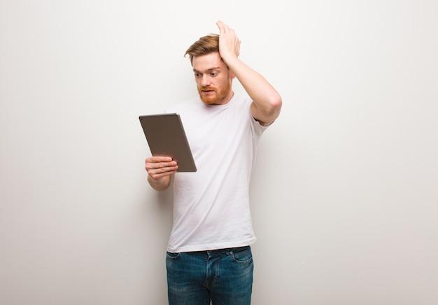 Homem jovem ruiva preocupado e oprimido e segurando um tablet