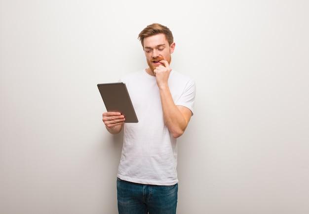 Homem jovem ruiva relaxado pensando em alguma coisa e segurando um tablet