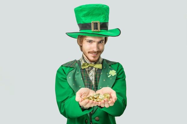 Homem jovem ruiva segurando muitas moedas de ouro nas mãos e mostrá-los para a câmera. ele olha para a frente. o cara usa o traje do santo patrick. isolado em cinza.