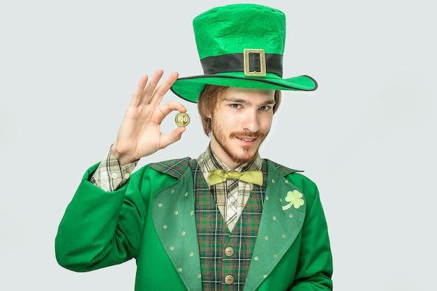 Homem jovem ruiva segurar moedas de ouro 100 e olhar. ele é muito feliz. o cara veste o traje verde de são patrício. isolado em cinza.