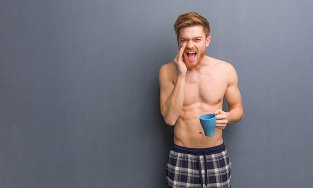 Homem jovem ruiva sem camisa gritando algo feliz para a frente.