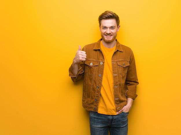 Homem jovem ruiva sorrindo e levantando o polegar para cima