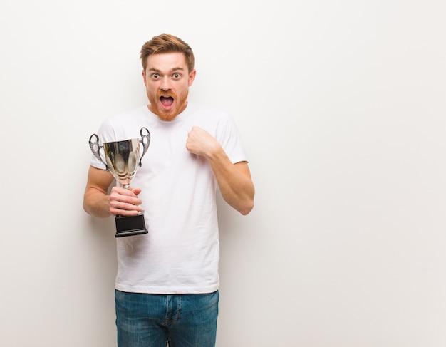 Homem jovem ruiva surpreso, sente-se bem sucedido e próspero. segurando um troféu.