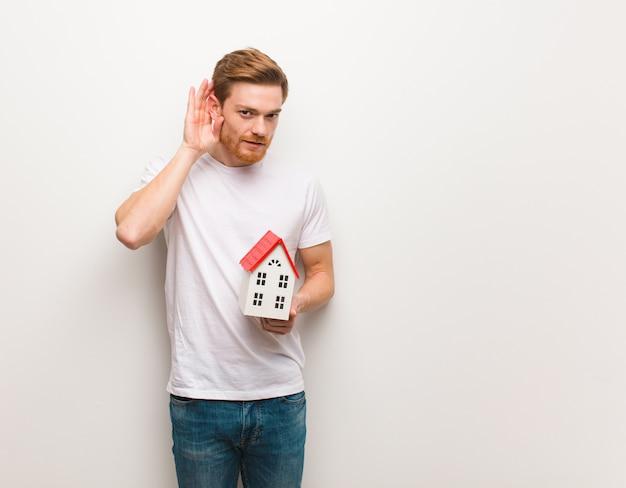 Homem jovem ruiva tentar ouvir uma fofoca. segurando um modelo de casa.