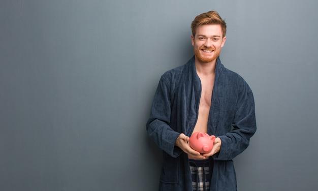 Homem jovem ruiva vestindo pijama alegre com um grande sorriso. ele está segurando um cofrinho.