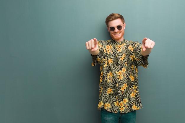 Homem jovem ruiva vestindo roupas de verão exóticas alegres e sorrindo apontando para frente