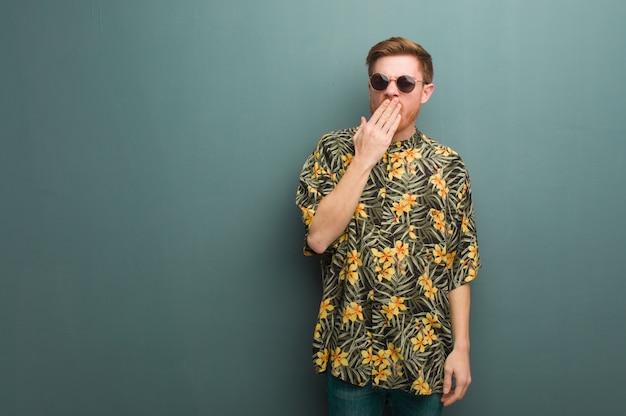 Homem jovem ruiva vestindo roupas de verão exóticas, cansado e com muito sono