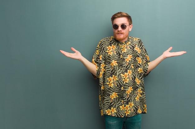 Homem jovem ruiva vestindo roupas de verão exóticas, duvidando e encolher os ombros