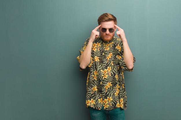 Homem jovem ruiva vestindo roupas de verão exóticas, fazendo um gesto de concentração