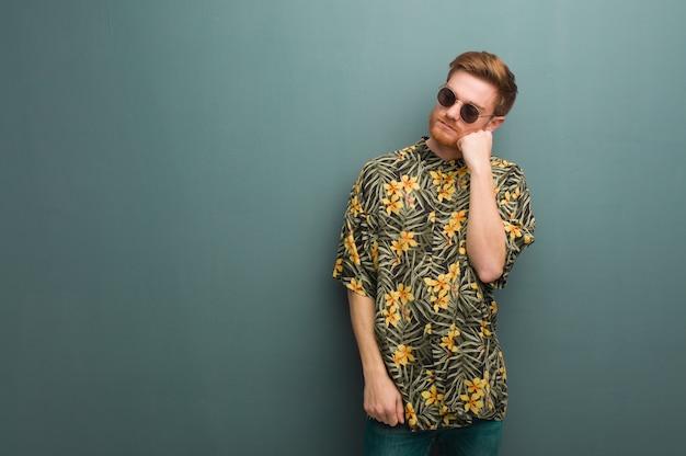 Homem jovem ruiva vestindo roupas de verão exóticas pensando em algo, olhando para o lado