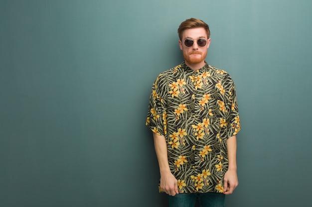 Homem jovem ruiva vestindo roupas de verão exóticas, pensando em uma idéia