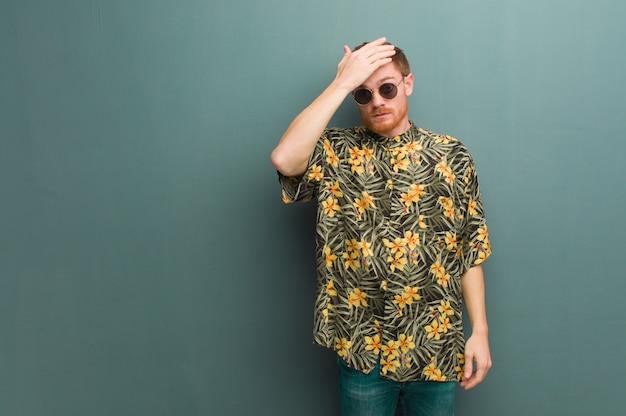 Homem jovem ruiva vestindo roupas de verão exóticas preocupado e oprimido
