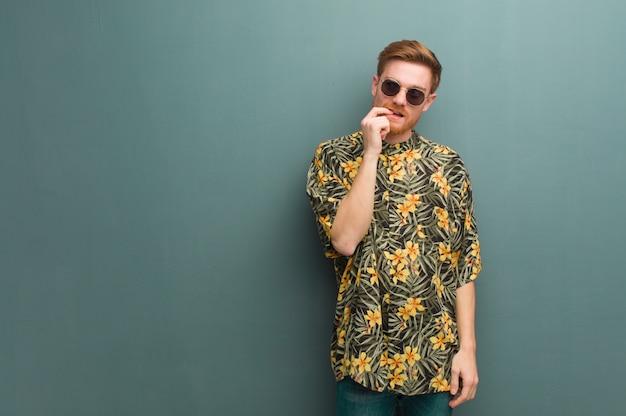 Homem jovem ruiva vestindo roupas de verão exóticas relaxado pensando em algo olhando para um espaço de cópia