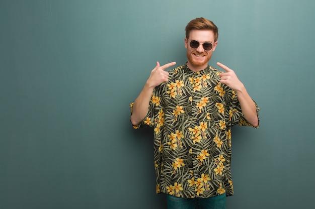 Homem jovem ruiva vestindo roupas de verão exótico sorrisos, apontando a boca