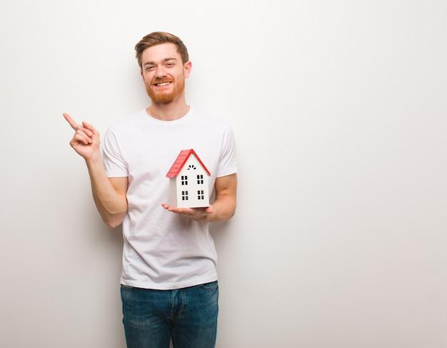Homem jovem ruivo apontando para o lado com o dedo. segurando um modelo de casa.
