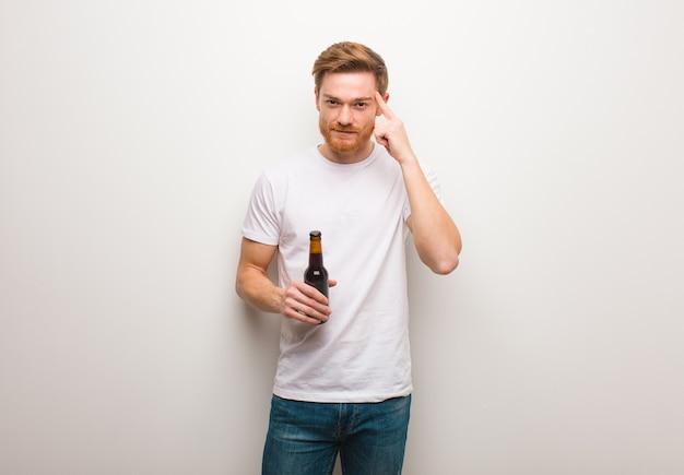 Homem jovem ruivo pensando em uma ideia. segurando uma cerveja.