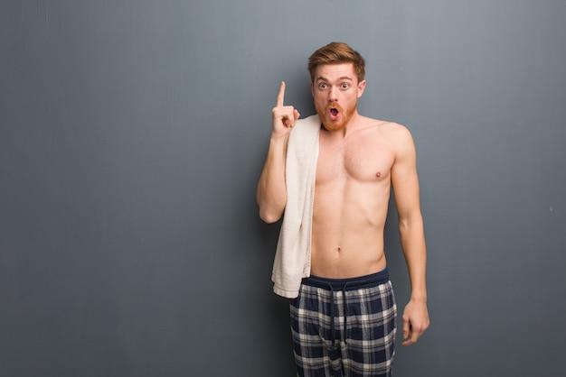 Homem jovem ruivo segurando uma toalha, tendo uma ótima ideia, o conceito de criatividade. ele está segurando uma toalha branca.