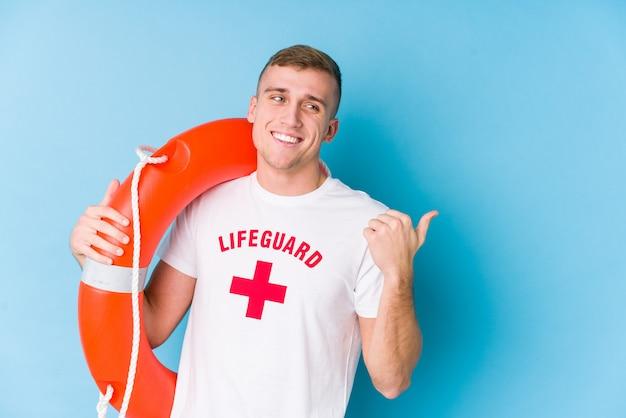 Homem jovem salva-vidas segurando uma bóia de resgate aponta com o dedo polegar, rindo e despreocupado.