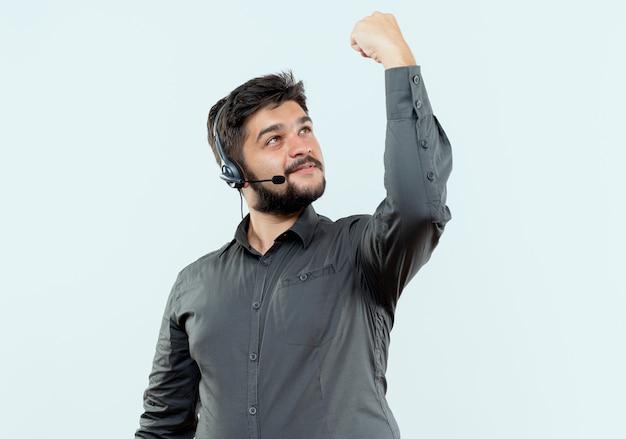 Homem jovem satisfeito do call center usando fone de ouvido levantando e olhando para o punho