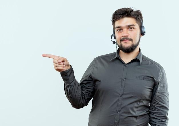 Homem jovem satisfeito do call center usando pontas de fone de ouvido na lateral, isolado no fundo branco com espaço de cópia