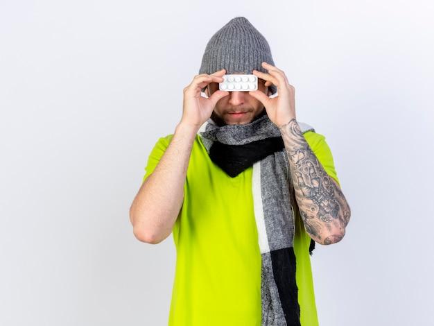 Homem jovem satisfeito e doente com chapéu e lenço de inverno segurando pacote de comprimidos médicos na frente dos olhos, isolados na parede branca