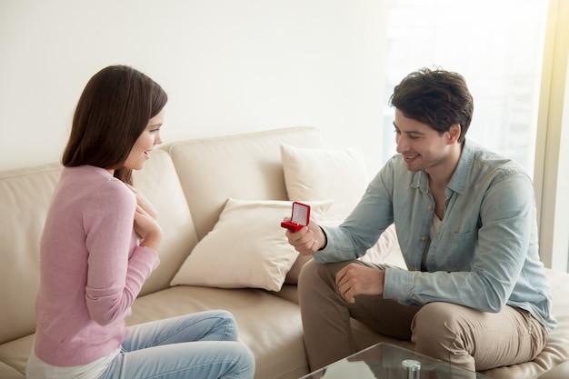Homem jovem, segurando, anel acoplamento, fazendo, proposta casamento