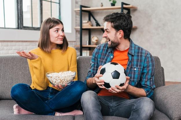 Homem jovem, segurando, bola futebol, em, mão, olhar, dela, namorada, segurando tigela, de, pipcorns