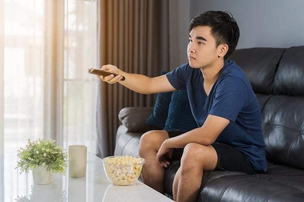Homem jovem, segurando, controle remoto, e, tv assistindo, enquanto, sentar sofá