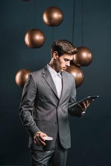 Homem jovem, segurando, copo descartável, olhar, tablete digital, ficar, frente, simplificado, espelho, redondo, cobre, lustre