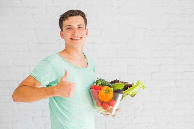 Homem jovem, segurando, legumes frescos, em, tigela vidro, mostrando, polegar cima, sinal