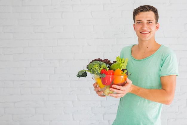Homem jovem, segurando, legumes frescos, em, tigela vidro