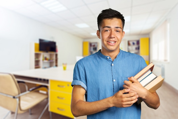 Homem jovem, segurando livros
